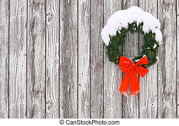 a snow covered lighted christmas wreath with a big red bow...