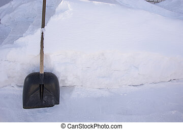 A snow shovel stands against a high snowdrift. Snow removal around the house. There is a lot of snow in the garden in winter.