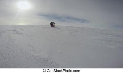 A snow trekker walks slowly - A steady shot of a man...