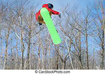 A snowboarder performs a mid-air trick in a terrain park
