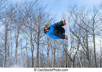 A snowboarder performs an aerial grab in a terrain park