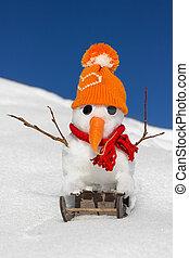 A snowman on a sled