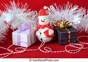 snowman posed next to gifts with shiny knots on a Christmas holiday deco