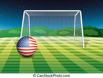 A soccer ball at the field with the flag of the United States