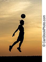 A soccer ball header at sunset.