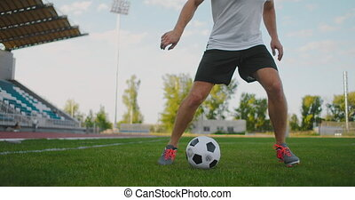 A soccer player at the stadium demonstrates dribbling with a...