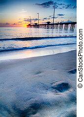 a, sol ascendente, olhadas, através, nuvens, e, é, refletido dentro, ondas, por, a, nags, cabeça, cais pescando, ligado, a, bancos exteriores, de, carolina norte