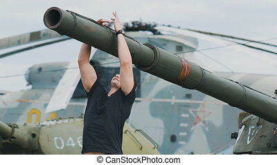 A soldier at a military base coach. He pulled on the gun of the tank. Strong man in military style.