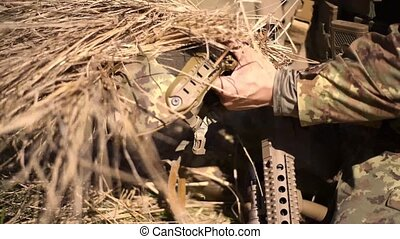 A soldier in a war scout puts dry grass in camouflage helmet...