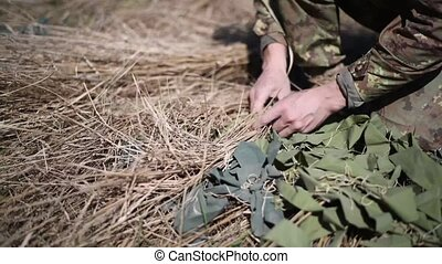 A soldier in a war scout puts dry grass in camouflage net to...