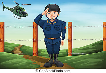A soldier in front of the barbwire fence
