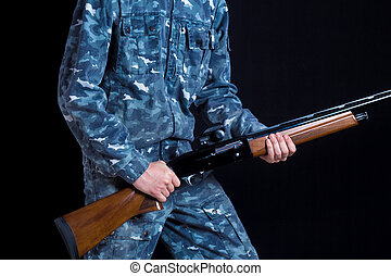 A soldier in military uniform with a shotgun. War games. Preparation for spring, autumn hunting. Soldier or hunter on a black background, isolated, copy space. Young man with a gun.