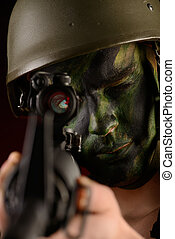 automatic rifles - A soldier in war paint looks through the...