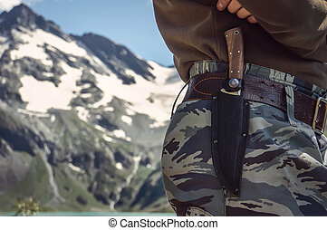 a soldier wearing camouflage clothing. The knife in its...