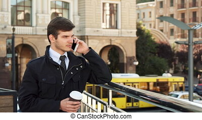 A solid man stands on the street and speaks on the phone