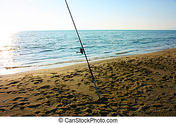 a solitary fishing rod rises from the ground on which it is planted on the sand of the beach and stands against the blue ocean sea