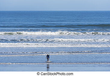 solitary surfer - a solitary surfer in front of the pacific...