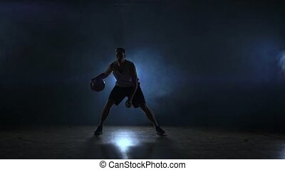 A solo basketball player does some dribbling moves in front...