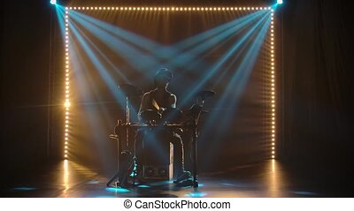 A solo performance by a musician drummer in a dark studio in...