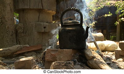 Close-up, low-angle still shot of a sooty kettle on a traditional smoky open fire-wood stone stove at a rural village in Kalaw, Myanmar