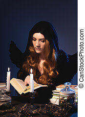 A sorceress in a black hooded cloak flatters a book surrounded by candles and witchcraft accessories