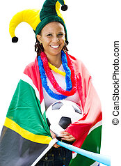 a south african soccer supporter wearing a fun hat and with the south african flag around her shoulders and holding a soccer ball and vuvuzela