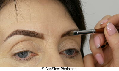 A special brush paints eyebrows with eyebrow shadows. Close view. Professional make-up artist doing makeup to middle-aged adult woman with beautiful blue eyes.