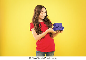 A special gift for her. Happy small child with blue gift pack on yellow background. Cute little girl holding gift box on boxing day. Adorable kid smiling with beautifully wrapped birthday gift box