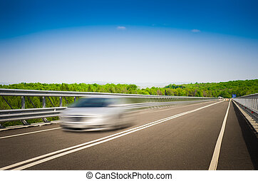 A speeding car on a highway on a sunny summer day with a blue sky and green forest on the background suggesting speed purity and power