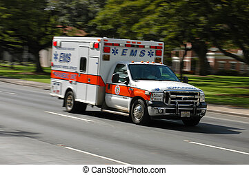 A speeding emergency medical services ambulance, with motion blur