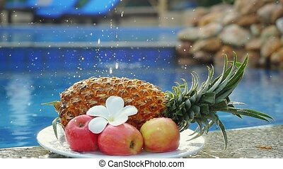 A splash of water dropping on a fruits Pineapple and Rose Apple and frangipani flower on the back of Swimming Pool in slow motion. Fresh Breakfast in Thailand.