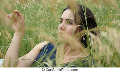 A splendid brunette girl lies in a field on a sunny day in...