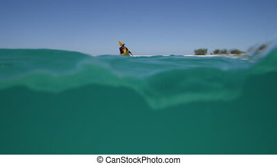 A split-shot of a kayaker - A wide slow motion shot in...