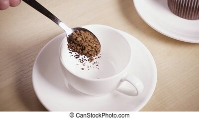 A spoon with coffee in a woman's hand is pouring into a cup slow motion