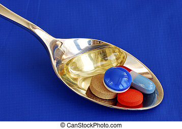 A spoonful of medicine including painkiller and vitamin isolated on blue