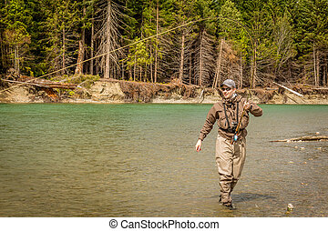 A sport fly fisherman hooked into a salmon on a river in British Columbia