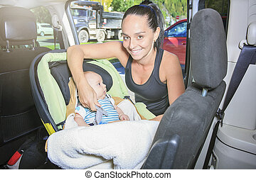 sport woman with a baby on his car.
