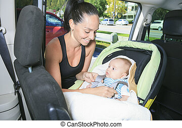 A sport woman with a baby on his car.