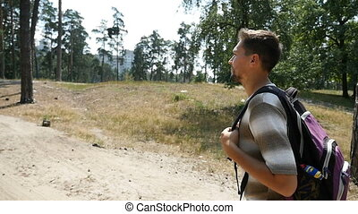 A sportive man with a backpack hikes in a pine forest in summer in slow motion