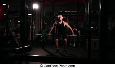 A sports athlete in the gym raises the bar with a weight above his head from the sitting position.