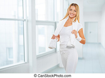 a sports female wearing sports clothes with white cottton towel