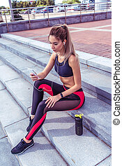 A sports girl in the city in summer, sits on stairs listening to music, writes a message on the phone, an online application on Internet, rest fitness and jogging workouts in the morning. Sportswear.