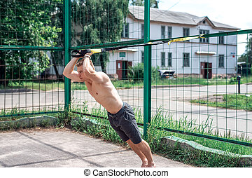 A sports person, the fresh air is engaged in training trx, sports clothes, the summer in the city, wringing out. Strength and stamina motivation.