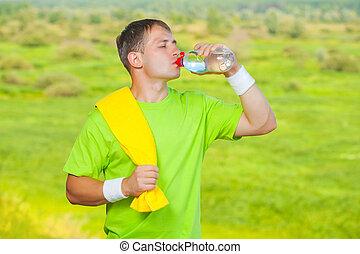 a sportsman drinking water from bottle