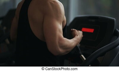 A sporty man runs on the treadmill in the gym