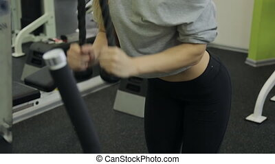 A sporty woman athlete performs triceps strain on hand in the gym.