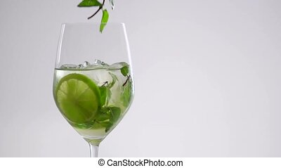 A sprig of mint falls on top of a cocktail in a glass.