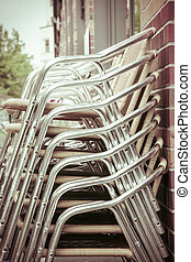 a stack of aluminum chairs from a restaurant