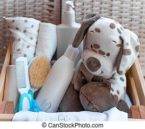 A stack of children's things, toys, pacifier in the wooden box Preparing for motherhood. Shopping for baby.