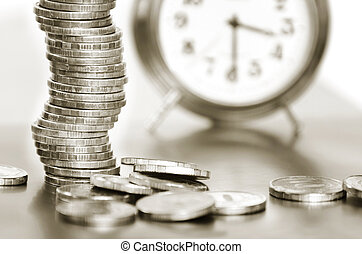 A stack of coins and alarm clock